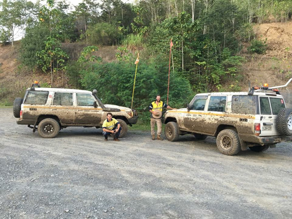 Two of our staff members posing with the vehicles after a day of data collection